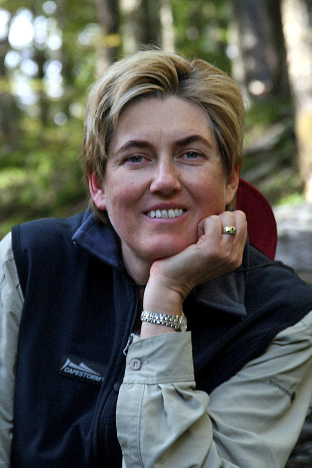 Darrell Farrow sat outside in a green forest, smiling at the camera with her chin propped up on her hand