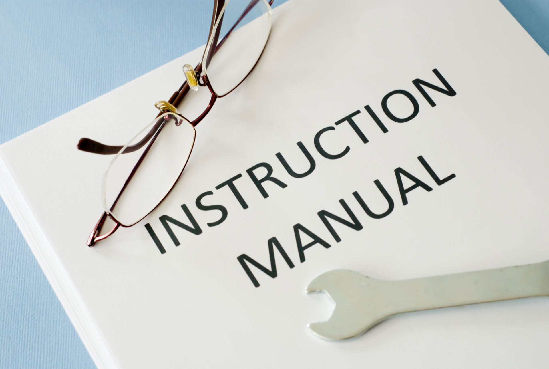 White instruction manual with a pair of spectacle and small wrench placed on top of the cover.