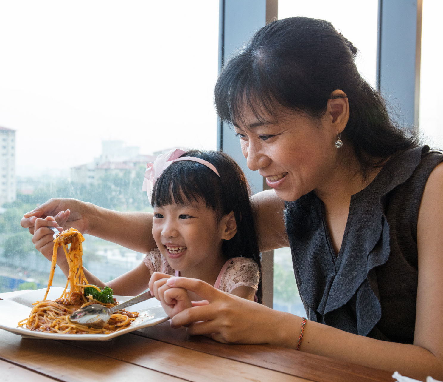 Smiling business woman at the dinner table with her young daughter, helping her eat a plate of noodles. Both are smiling and enjoying quality time together.