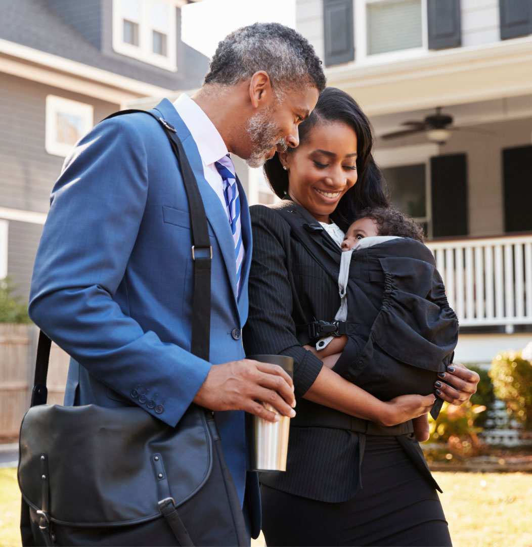 Happy professional couple outside their home dressed in business suits and admiring their baby who's looking up at them from a black baby carrier on the mother's chest