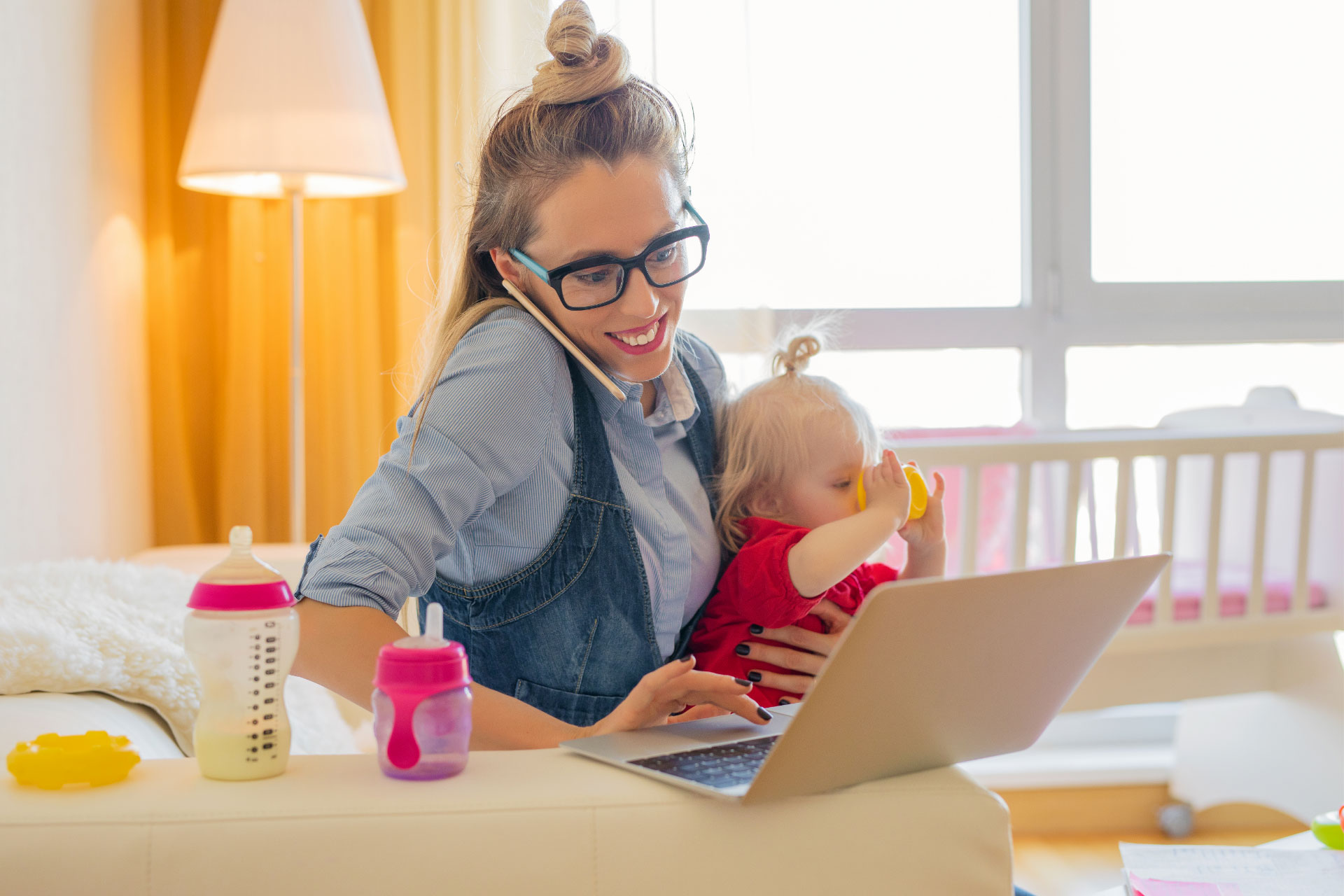 Smiling mother multitasking at home as she is sat on a couch working on her laptop, talking on her phone and holding her baby who is sipping from a cup