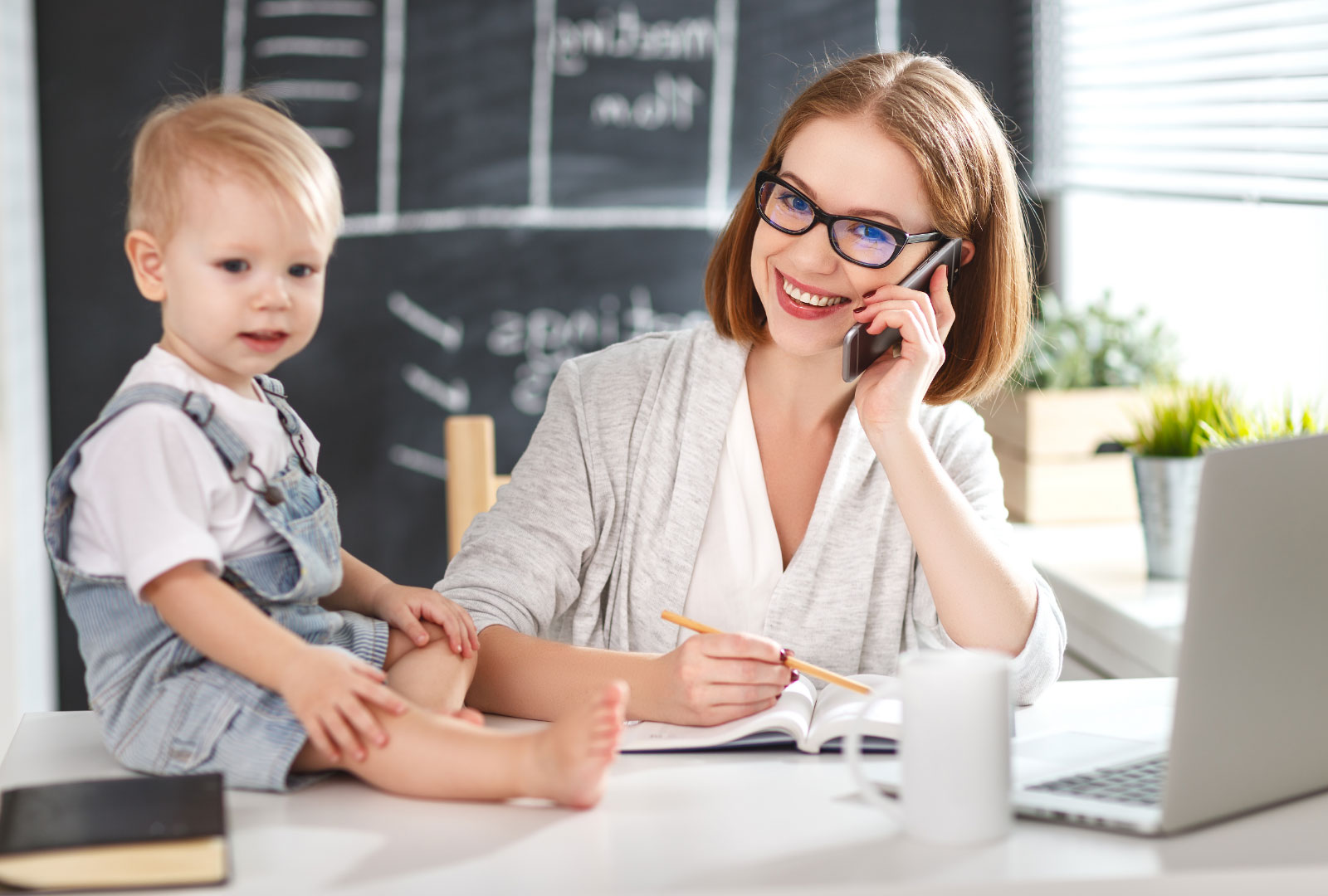 Smiling professional mother is multitasking at home with her laptop open as talks on her phone and supervises her toddler who is content and sat on the desk in front of her
