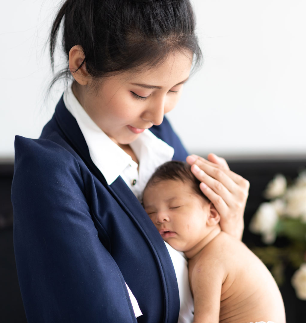 Young mother at home wearing a navy business suit while adoringly looking down at her sleeping newborn baby who is carefully cradled against her chest